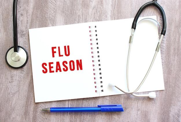 빨간색 텍스트 flu season이 있는 흰색 노트북과 회색 나무 테이블에 청진기가 있습니다.