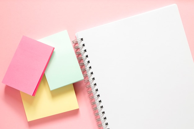 White notebook with a spiral and three multi-colored stickers on a delicate pink