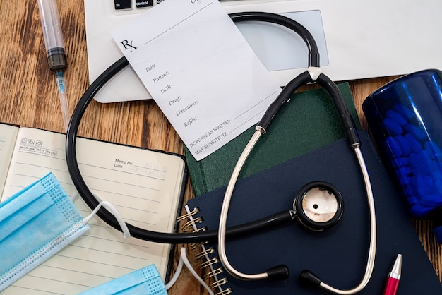 White notebook with stethoscope prescription from doctor on black keyboard with notebook masks on the table. medicine concept
