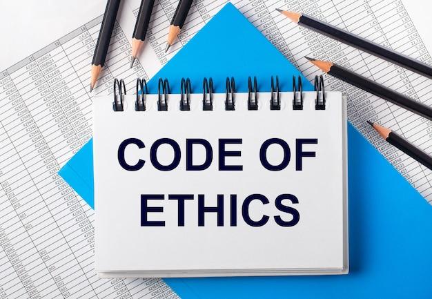 青い背景とレポートの黒い鉛筆の横にあるテーブルに「倫理規定」というテキストが書かれた白いノート。ビジネスコンセプト