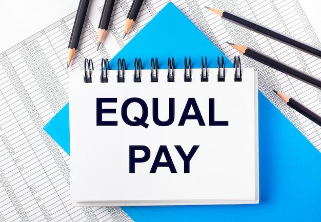 Белый блокнот с текстом equal pay на столе рядом с черными карандашами на синем фоне и отчетами. бизнес-концепция