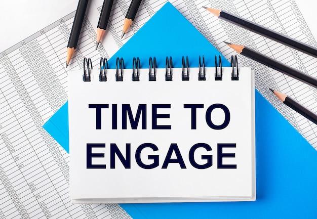 青い背景とレポートの黒い鉛筆の横にあるテーブルに「timetoengage」というテキストが書かれた白いノートブック。ビジネスコンセプト