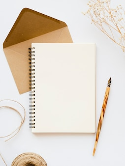 White notebook with a wooden  nib on a pale brown envelope with a brown thread and a branch on a white background