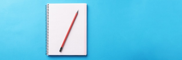 White notebook with wooden pencil lies on blue background