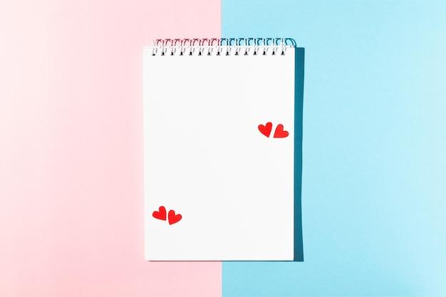 ピンクに赤いハートのメモ用の白いメモ帳とバレンタインデーの年の背景のグリーティングカード