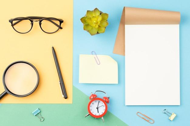 青い背景に白いメモ帳メガネ鉛筆
