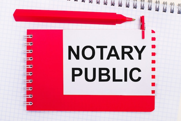 On a white notepad, a red pen, a red notepad and a white sheet of paper with the text notary public