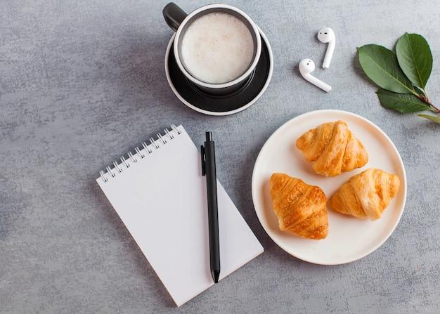 Белый блокнот, беспроводные наушники, кофейная кружка. концепция онлайн-обучения, работы из дома, домашнего офиса.