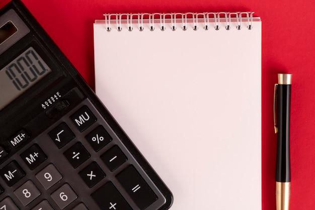 빨간색 배경에 계산기와 세련된 펜이 있는 흰색 메모장. 공간을 복사합니다.