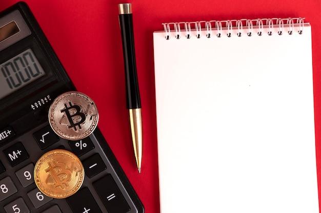 빨간색 배경에 계산기, 세련된 펜, 비트코인 동전이 있는 흰색 메모장. 공간을 복사합니다.