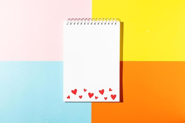 ピンク、黄色、青、オレンジ色の背景のコピースペースに赤いボール紙のハートと白いメモ帳