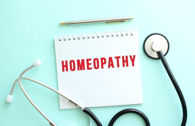 파란색 배경에 빨간색 텍스트 homeoparthy와 청진기가 있는 흰색 메모장.