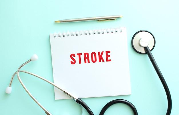 파란색 배경에 빨간색 텍스트 스트로크와 청진기가 있는 흰색 메모장. 의료 개념