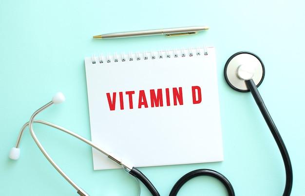 파란색 배경에 빨간색 텍스트 vitamin d와 청진기가 있는 흰색 메모장. 의료 개념