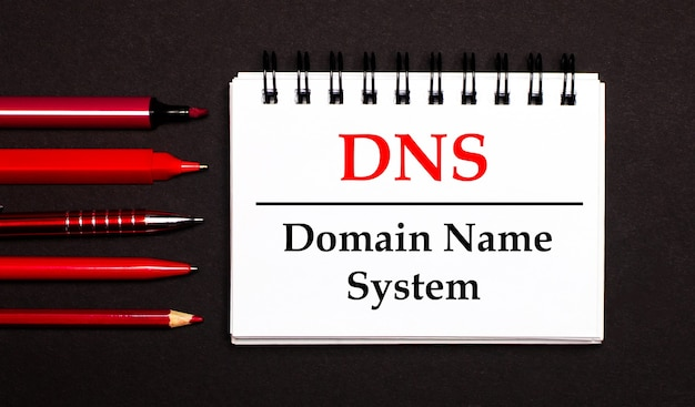 A white notepad with the text dns domain name system, written on a white notepad next to red pens, pencils and markers on a black surface