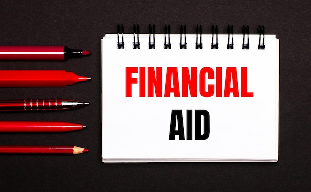 A white notepad with the text financial aid, written on a white notepad next to red pens, pencils and markers on a black background.