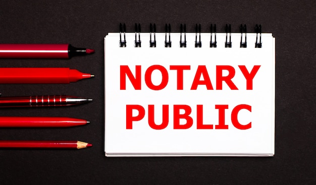 A white notepad with the text notary public, written on a white notepad next to red pens, pencils and markers on a black background.