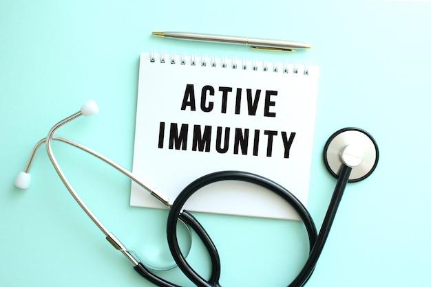파란색 배경에 active immunity라는 단어와 청진기가 있는 흰색 메모장.