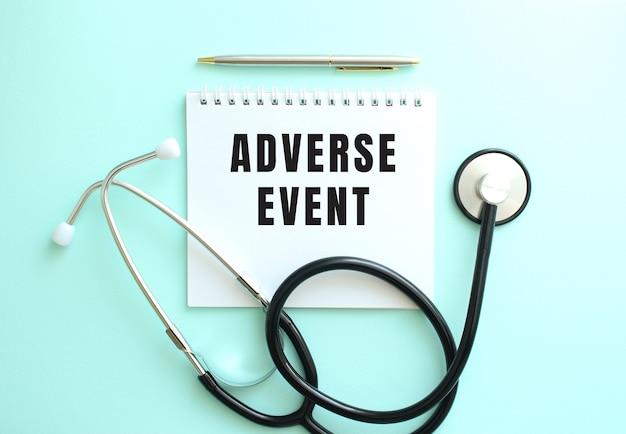 Adverseeventという言葉と青い背景に聴診器が付いた白いメモ帳