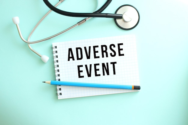 Adverseeventという言葉と青い背景に聴診器が付いた白いメモ帳。