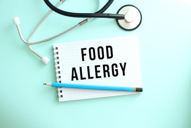 음식 알레르기라는 단어와 파란색 배경에 청진기가 있는 흰색 메모장