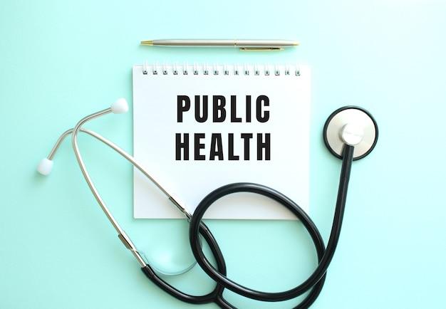 파란색 배경에 public health라는 단어와 청진기가 있는 흰색 메모장.
