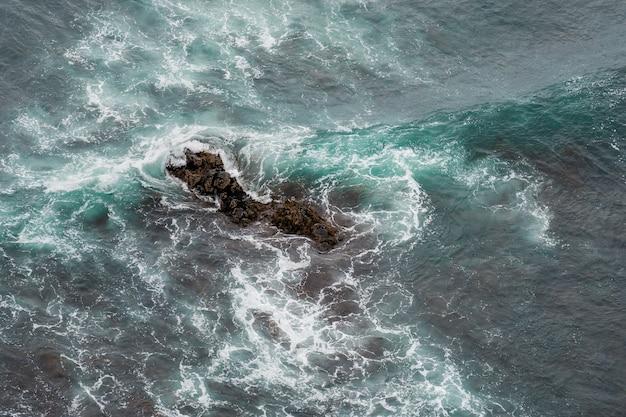 夏に海岸の海の岩に打ち寄せる白い海の波。