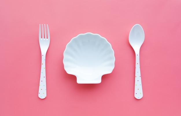 皿の貝とスプーンの白、色の背景にフォーク