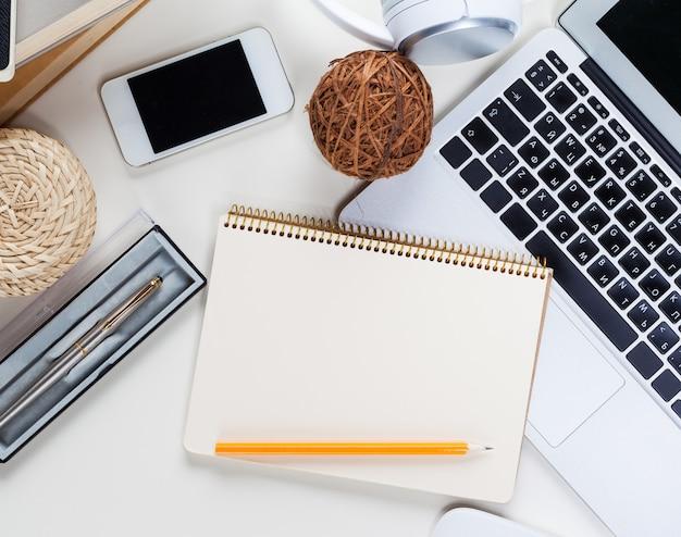 多くのものが置かれた白いオフィスデスクテーブル。上面図