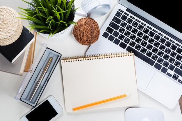 たくさんのものが置かれた白いオフィスデスクテーブル。上面図