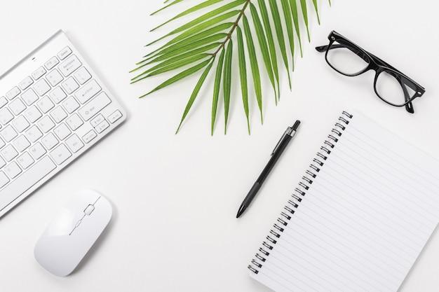 空白のノートブック、コンピューターのキーボード、その他の事務用品と白いオフィスデスクテーブル。コピースペースの平面図です。