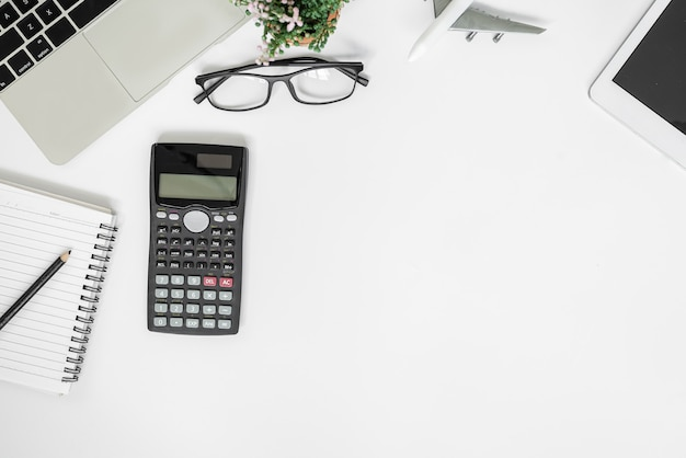 White office desk. table with blank notebook, tablet, calculator, computer and other office supplies