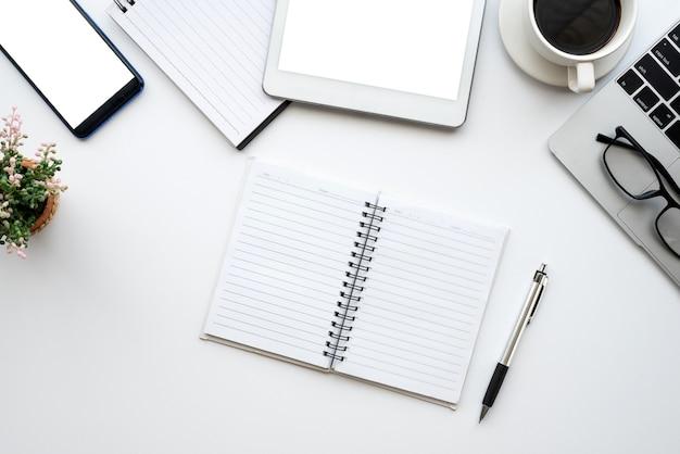 白いオフィスデスク。空白のノートブック、タブレット、コンピューター、その他の事務用品を備えたテーブル。コピースペースのある上面図。