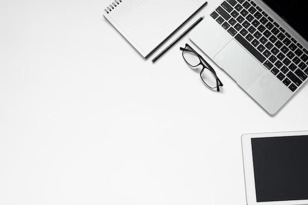 白いオフィスデスク。空白のノートブック、タブレット、メガネ、電卓、コンピューター、その他の事務用品を備えたテーブル。コピースペースのある上面図。