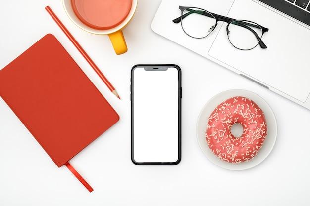 スマートフォンの空白の画面と白いオフィスデスクテーブル