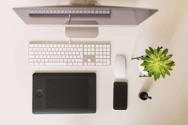 White office desk table with computer keyboard, mouse, monitor, graphic tablet, smartphone, succulent plant and other office supplies.
