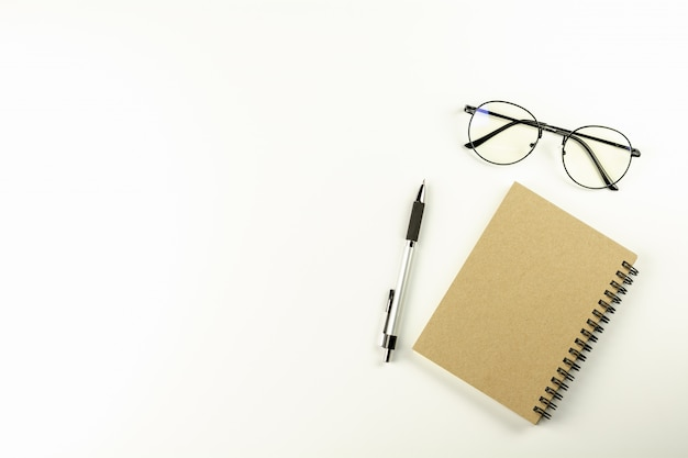 White office desk table with glasses, pen and a brown notebook