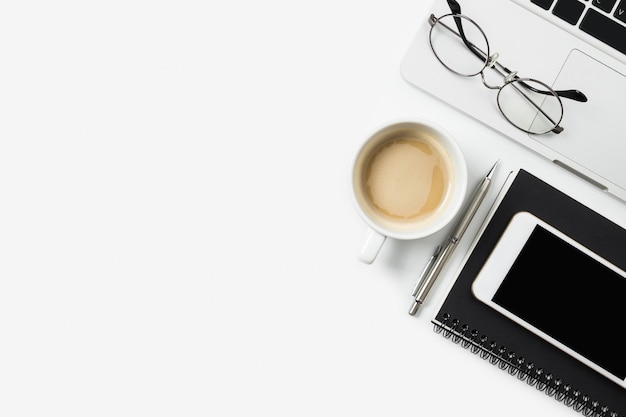 White office desk table with laptop, cup of coffee and supplies in flat lay.