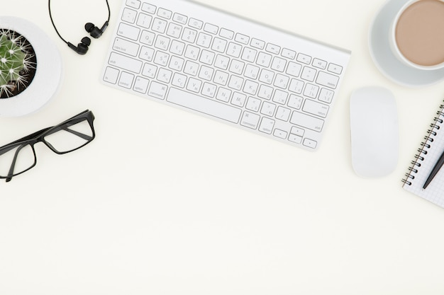 ノートパソコン、一杯のコーヒー、用品と白いオフィスデスクテーブル。コピースペースのトップビュー。