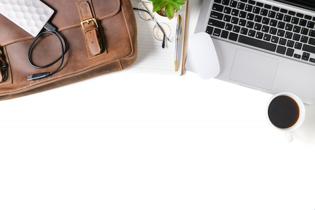 White office desk table with laptop, notebook and vintage bag