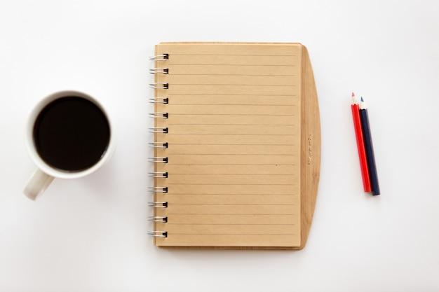 ノートブックと鉛筆、コーヒーを備えた白いオフィスデスク