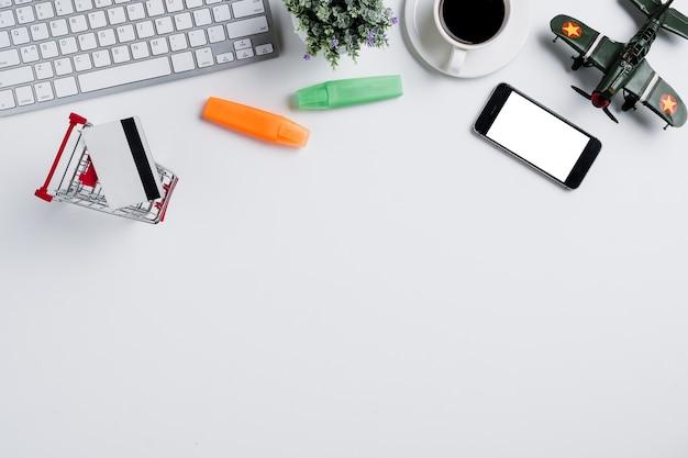 Белый офисный стол с компьютерной клавиатурой, ноутбуком и расходными материалами