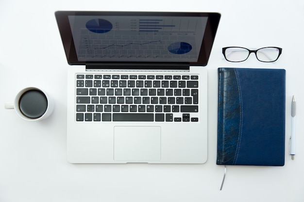White office desk with glasses, laptop, coffee and notebook