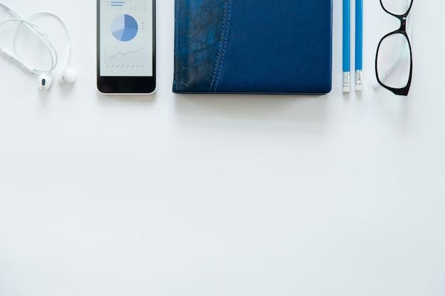 Белый офисный стол с очками, мобильный телефон, наушники