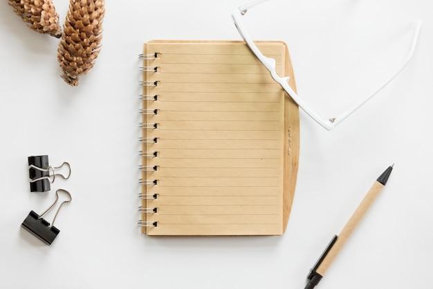 Белый офисный стол с очками, ручкой, записной книжкой и конусом