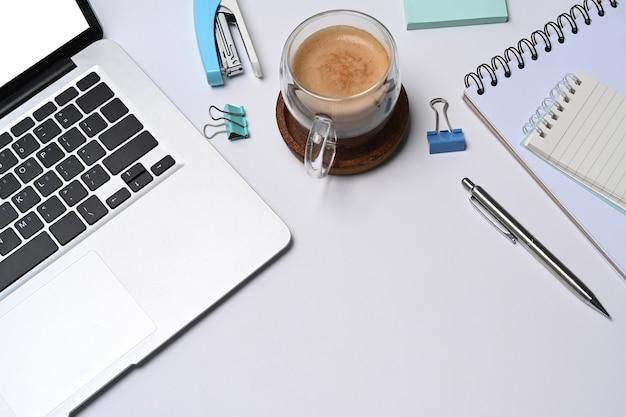 Белый офисный стол с портативным компьютером, ноутбуком и чашкой кофе.