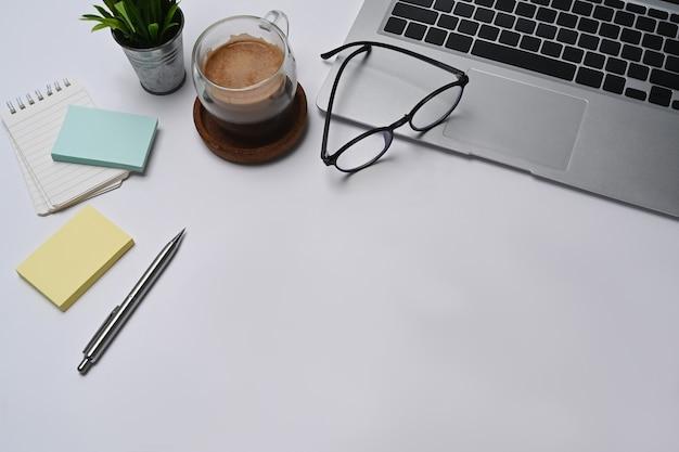 Белый офисный стол с портативным компьютером, заметками, очками и чашкой кофе.