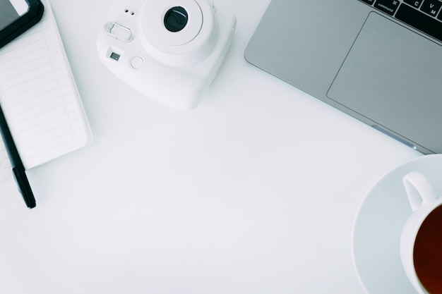 White office desk with laptop, notebook with pen, mini camera and cup of tea