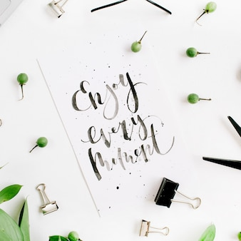 White office desk with quote enjoy every moment, green leaves and office supplies on white surface