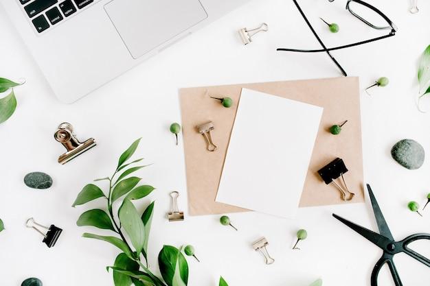 紙の空白と緑の葉と白いオフィスデスクワークスペース